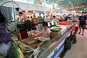 A young girl reads a children's book at her parents' vegetable stall at a food market in Shanghai, China on 31 July 2012.