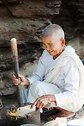 A female Buddhist monk, a Bhikkhunis, prepares food in rural Cambodia