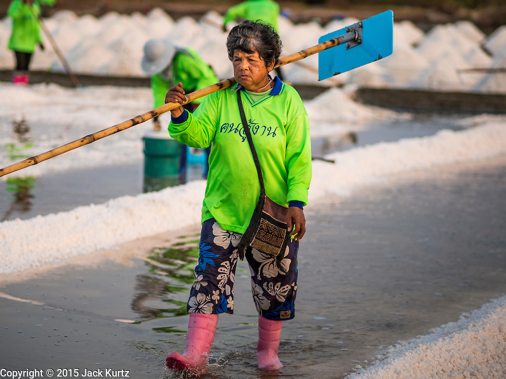 09 MARCH 2015 - NA KHOK, SAMUT SAKHON, THAILAND:  A worker walks through a salt pond after raking sea salt into mounds during the salt harvest in Samut Sakhon. The coastal provinces of Samut Sakhon and Samut Songkhram, about 60 miles from Bangkok, are the center of Thailand's sea salt industry. Salt farmers harvest salt from the waters of the Gulf of Siam by flooding fields and then letting them dry through evaporation, leaving a crust of salt behind. Salt is harvested through dry season, usually February to April. The 2014 salt harvest went well into May because the dry season lasted longer than normal. Last year's harvest resulted in a surplus of salt, driving prices down. Some warehouses are still storing salt from last year. It's been very dry so far this year and the 2015 harvest is running ahead of last year's bumper crop. One salt farmer said prices are down about 15 percent from last year.   PHOTO BY JACK KURTZ