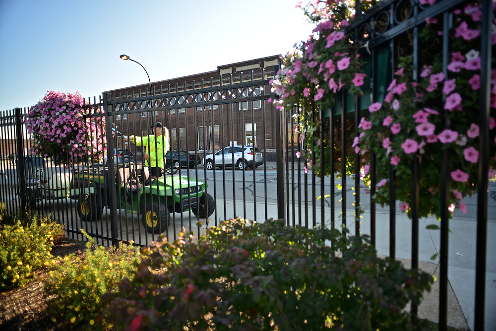 A Downtown Akron Partnership clean & safety ambassador watering hanging flower baskets.