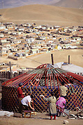 In late September, a family assembles a ger (round tent built from canvas, strong poles, and wool felt) in a squatter settlement on the hillsides of Ulaanbaatar, Mongolia. They have been herding animals in the countryside for the summer and are now moving back into the city for the winter. Despite the popular image of Mongolians as nomadic herders, it is an increasingly urbanized country. More than one quarter of Mongolians live in the capital city, Ulaanbaatar. Material World Project.