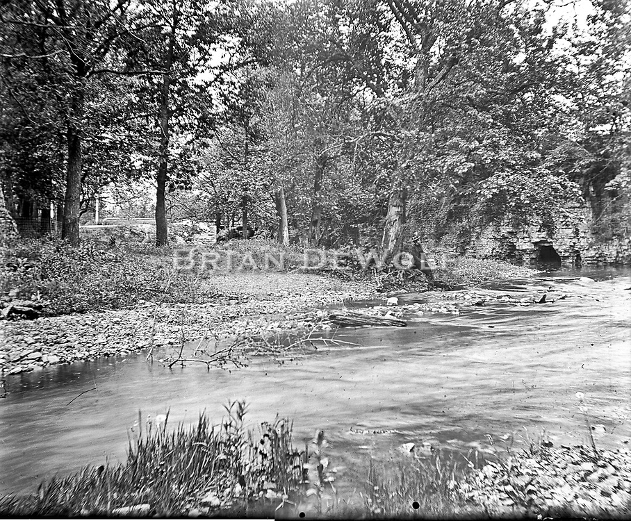 """This location has been identified by seeing the same scene on page 82 of John Gustafson's """"Historic Batavia"""". This is Mill Creek Park. <br /> <br /> The RR bridge over a creek seen in one of the other pictures is surely the bridge in the background of this picture. The bridge design is the same and the fence post near the bridge has a ball on it as does a fence post in the other photo."""
