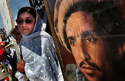 KABUL,AFGHANISTAN - SEPT. 9: An Afghan girl holds a portrait of slain leader Ahmad Shah Massoud during a ceremony in Kabul Sports Stadium September 9, 2002  to comemerate the anniversary of his death  in Kabul, Afghanistan. (Photo by Ami Vitale/Getty Images)