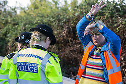 Metropolitan Police officers arrest an Insulate Britain climate activist who had previously blocked a M25 slip road at Junction 14 close to Heathrow airport as part of a campaign intended to push the UK government to make significant legislative change to start lowering emissions on 27th September 2021 in Colnbrook, United Kingdom. The activists are demanding that the government immediately promises both to fully fund and ensure the insulation of all social housing in Britain by 2025 and to produce within four months a legally binding national plan to fully fund and ensure the full low-energy and low-carbon whole-house retrofit, with no externalised costs, of all homes in Britain by 2030.