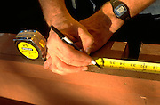 Close up of hands age 50 measuring wood with tape measure.  Nisswa  Minnesota USA