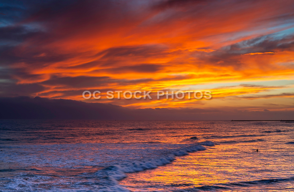 Surfer Sitting In The Water Under A Red Sky Sunset