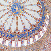 The ornate decorations of the walls and ceiling inside the prayer hall of Istanbul's Blue Mosque. While it is widely known as the Blue Mosque for the its interior tiling, the mosque's formal name is Sultan Ahmed Mosque (or Sultan Ahmet Camii in Turkish). It was built from 1609 to 1616 during the rule of Sultan Ahmed I.