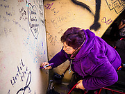 21 APRIL 2017 - CHANHASSEN, MN: FELIZ KEDINEOGLU, (left) from Los Angeles, writes a note to Prince in the pedestrian tunnel in front of Paisley Park, his former home and recording studio. The tunnel has become a memorial to Prince, people have drawn graffiti in the tunnel honoring him and they leave memorials in the tunnel. The superstar died from an accidental overdose of the opioid fentanyl on April 21, 2016. Friday was the first anniversary of his death. Crowds of people gathered at Paisley Park, which is now a museum, to honor the Minnesota born musician.     PHOTO BY JACK KURTZ