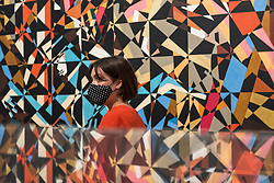 "© Licensed to London News Pictures. 15/10/2020. LONDON, UK.  London, UK. 15 October 2020. A staff member is seen reflected in front of ""In the Hold"", c. 1913-14, by David Bomberg. The work is part of new displays in Tate Britain's three collection routes: Rothko and Turner (a new route to celebrate 50 years since Mark Rothko first gave Tate his iconic Seagram Murals to join paintings he so admired by JMW Turner), British Art 1540-1920 and British Art 1930-Now.  Visitors may book online for free to visit the museum.  Photo credit: Stephen Chung/LNP"