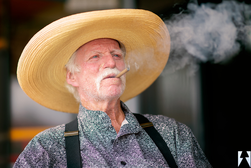 White haired cowboy in a straw sombrero and black suspenders sitting back enjoying a stogie with a big puff of smoke.