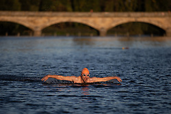 © Licensed to London News Pictures. 01/10/2018. London, UK. A swimmer swims in the Serpentine Lido in Hyde Park at sunrise this morning. Temperatures in the capital were cold this morning, but are set to reach over 20 degrees Celsius later this week, higher than average for the time of year. Photo credit : Tom Nicholson/LNP