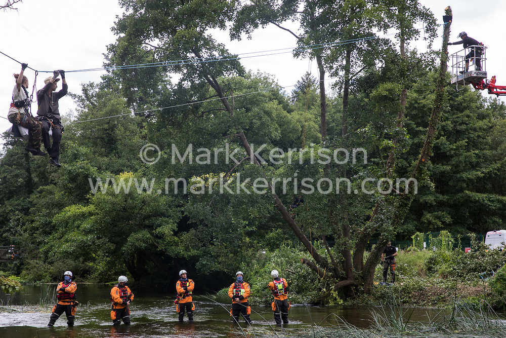 Denham, UK. 24 July, 2020. Swan (l) and Larch (r), environmental activists from HS2 Rebellion, observe a tree surgeon working with the National Eviction Team from a line above the shallow river Colne attached to an ancient alder tree which they were trying to protect from destruction in connection with works for the HS2 high-speed rail link in Denham Country Park. A large policing operation involving the Hampshire Police Marine Support Unit (seen here), Metropolitan Police, Thames Valley Police and City of London Police as well as the National Eviction Team was put in place to enable HS2 to remove the tree.
