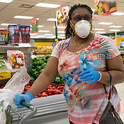 Gloves and a face mask are seen on a shopper at Fancy Fruit and Produce grocery store on Friday, April 3, 2020 in Orlando, Florida. (Alex Menendez via AP)