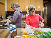"26 FEBRUARY 2020 - FARMINGTON, MINNESOTA: ALIA TOBIN, right, and MARY SUE BRIGGS, both from Farmington, volunteers at the community dinner at Faith Church, work in the kitchen before the dinner. Faith Church is a United Methodist Church in Farmington, MN, about 30 minutes south of the Twin Cities. The dinner is sponsored by Loaves & Fishes, a Christian organization that provides food for community dinners and foodbanks. Farmington, with a population of 21,000, is a farming community that has become a Twin Cities suburb. The city lost its only grocery store, a Family Fresh Market, in December, 2019. The closing turned the town into a ""food desert."" In January, Faith Church started serving the weekly meals as a response to the store's closing. About 125 people per week attend the meal at the church, which is just a few blocks from the closed grocery store. The USDA defines food deserts as having at least 33% or 500 people of a census tract's population in an urban area living 1 mile from a large grocery store or supermarket. Grocery chains Hy-Vee and Aldi both own land in Farmington but they have not said when they plan to build or open stores in the town.     PHOTO BY JACK KURTZ"