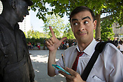 Living statue street performers hanging out during a break from standing still. This Mr Bean performer makes some adjustments to his look with his make up and mirror. The South Bank is a significant arts and entertainment district, and home to an endless list of activities for Londoners, visitors and tourists alike.