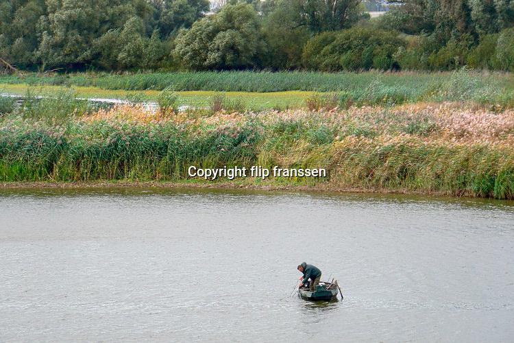 Nederland, Ooioj, 24-10-2019Op de Oude Waal is een visser, sportvisser, bezig met zijn spullen . Het is  mooi weer voor de tijd van het jaar . Sportvisserij,bootje,roeibootFoto: Flip Franssen