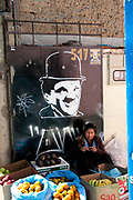 Bolivia June 2013. La Paz. Woman knitting and selling fruit in front of a Charlie Chaplin wall painting.
