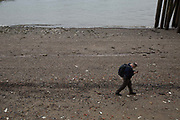 A man walks along the Thames Beach, opposite Gabriels Wharf, looking at his mobile phone on 19th February 2017 in London, United Kingdom. From the series Our Small World, an observation of our mobile phone obsessions