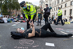 © Licensed to London News Pictures. 01/09/2020. London, UK. A police officer speaks to an Extinction Rebellion protester during demonstration in Parliament Square. The environmental activist group intend to peacefully blockade the Houses of Parliament until Parliament agrees to debate their three demands.  Photo credit: George Cracknell Wright/LNP