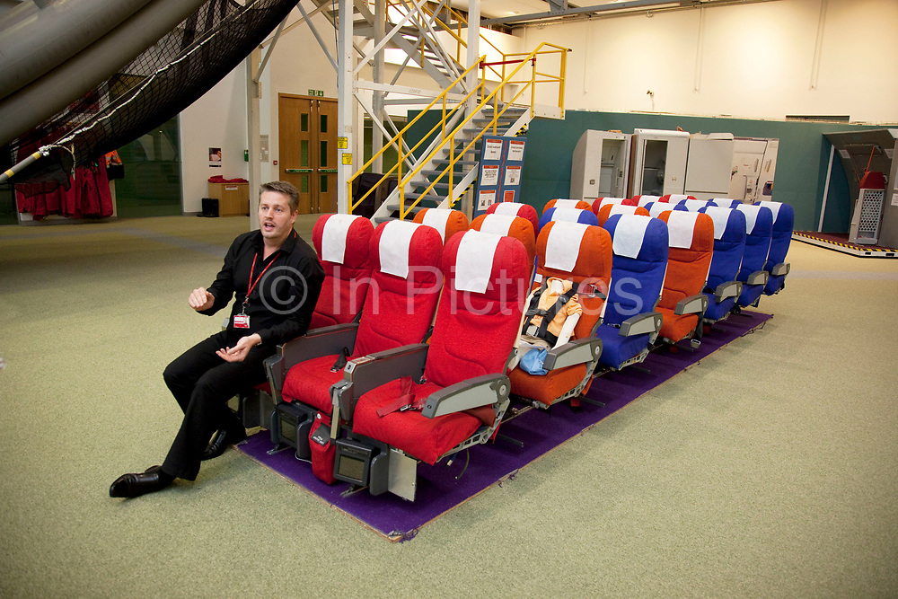 Safety training instructor sits on a mock up of a row or aircraft seats.  Virgin Atlantic air stewardess and steward training at The Base training facility in Crawley. Potential hostesses are put through a gruelling 6 week training program, during which they are tested to their limits. With exams every day requiring an 88% score to pass. The Base is a modern environment for a state of the art airline training situated next to Virgin Atlantic's HQ.