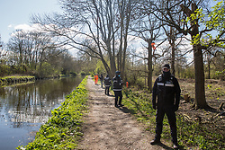 National Eviction Team (NET) enforcement agents stand on the towpath alongside the Grand Union Canal during tree felling in Denham Country Park for electricity pylon relocation works connected to the HS2 high-speed rail link on 6th April 2021 in Denham, United Kingdom. Large swathes of the Colne Valley have been cleared of trees and vegetation for HS2 works which will include the construction of a Colne Valley Viaduct across lakes and waterways.