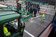A construction worker carries a tube across the road in front of schoolboys at Lambeth North, on 27th March 2019, in London, England
