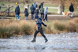 © Licensed to London News Pictures. 13/02/2021. London, UK. A child jumps over the ice as families play on frozen fields that were flooded by Storm Darcy last week. Members of the public gather on the last day of freezing temperatures in Richmond Park, South West London before warmer weather rolls in on Monday with highs of 12c as the government mulls over its road map for unlocking the country from Covid-19 restrictions. Photo credit: Alex Lentati/LNP