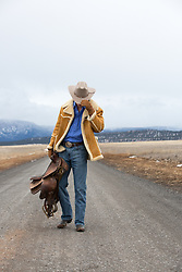 cowboy walking on a dirt  road with a saddle