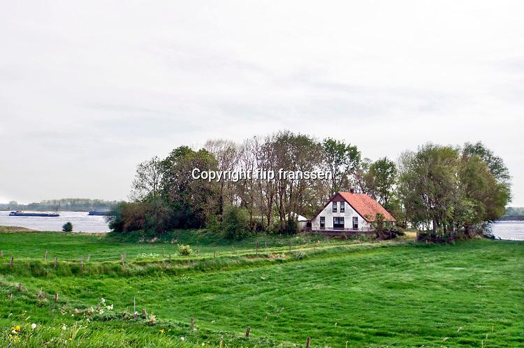 Nederland, Andelst, 23-4-2019Een huis ligt buitendijks op een verhoging in de uiterwaarden van de rivier de Waal . Bij hoogwater zal het omringd worden door water.Foto: Flip Franssen