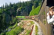 Alaska, Skagway passenger on the White Pass Railroad train enjoys the scenery