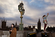 With the winter landscape of Westminster and the Houses of Parliament on the river Thames opposite, tourists visit London including a woman with a David Bowie bag standing on the anti-terrorism security barriers at the southern end of Westminster Bridge, to take a picture of the London Eye, on 8th November 2017, in Lambeth, London.