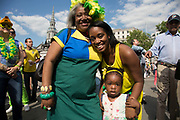 London, UK. Thursday 12th June 2014. Three generations. Brazilians gather for the Brazil Day celebrations in Trafalgar Sq. A gathering to celebrate the beginning of the Brazil 2014 FIFA World Cup. Revellers sing and dance and play football games and all in the yellow green and blue of the Brazilian flag.