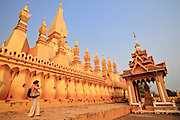 Mar. 11, 2009 -- VIENTIANE, LAOS:  A tourist takes photos of Pha That Luang in Vientiane, Laos, is the most important national monument in Laos. Construction was started by King Setthathirat in 1566. The complex was sacked and destroyed by the Siamese (Thais) in 1828 and restored by the French starting in 1900.  Photo by Jack Kurtz / ZUMA Press