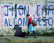 An Andean woman with blue dress, red sweater, and felt hat walks on sidewalk by whitewashed wall painted with political ad, in Huaraz, Peru, South America.