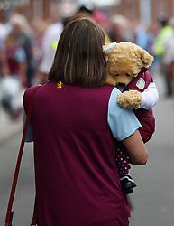 An Aston Villa fan carries a teddy bear to the game