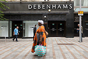 On the Kirkgate high street, people carrying shopping bags pass by a permanently closed branch of the department store Debenhams on 17th June, 2021 in Leeds, United Kingdom. The popular British retailer was forced to close all of its stores after the Coronavirus pandemic battered the countrys retail sector, ending the brands 242-year run as a mainstay of Britains high streets; it is now an online retail brand owned by fashion behemoth Boohoo.