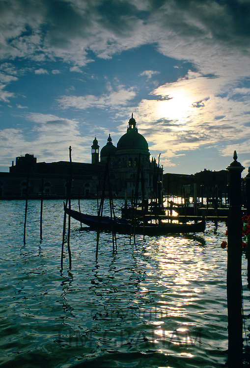 Canals of Venice at daybreak with gondolas and the Church of Santa Maria Della Salute silhouetted against the sky, Italy