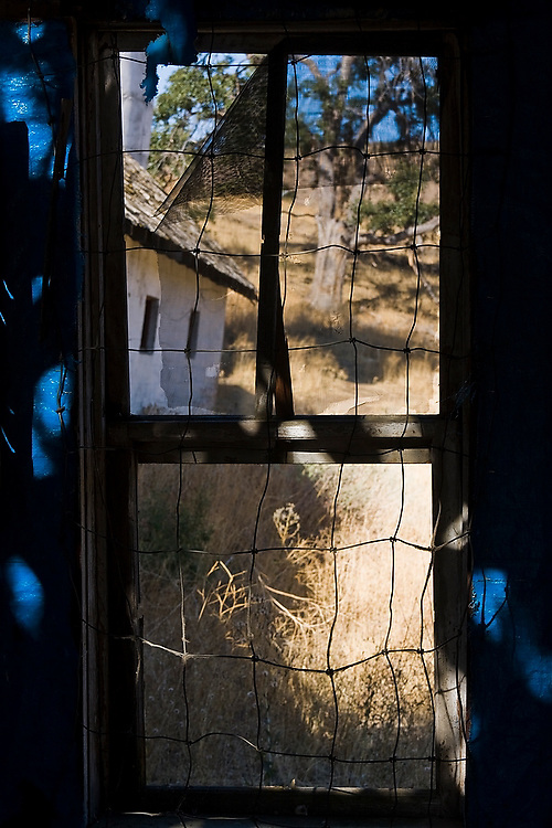 A dilapidated window frames the barn, tree and dry grasses of an abandoned farm by the shores of the Yakima River near Cle Elum, Washington.