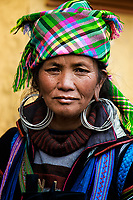 Hmong Woman: A woman, of a local Hmong hill tribe, wearing a mixture of modern and traditional clothing, as well as  numerous large silver earrings, Sapa Vietnam.