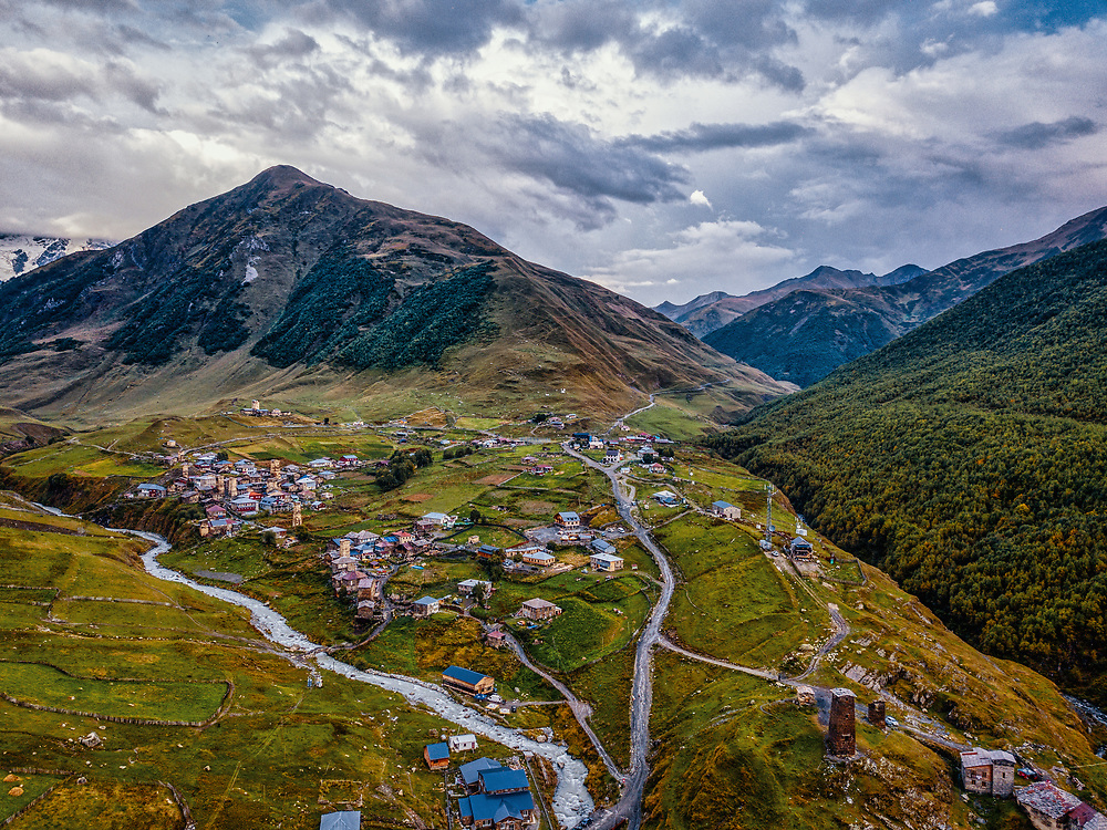 Drone shot of Ushguli in Georgia. Landscape with mountains and cloudy sky, river, villages
