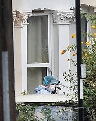 © Licensed to London News Pictures. 18/08/2018. Catford, UK. An investigator in a protective suit gathers evidence outside a property where a man in his 50's has been stabbed to death in Catford, south London. Police were called at 4am, the victim was pronounced dead at the scene at 5.28am. No arrests have been made. Photo credit: Peter Macdiarmid/LNP