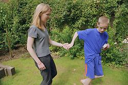 Teenage boy with autism leading carer across garden,