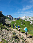 Hikers at Bötzel pass contemplate the distant peak of Santis, in Switzerland, Europe. Shared by three cantons, Säntis (2502 m) is the highest mountain in the Alpstein massif of northeastern Switzerland, and highest of the Appenzell Alps, which rise between Lake Walen and Lake Constance. Accessible via cable car or spectacular trails, Säntis provides a spectacular view across six countries: Switzerland, Germany, Austria, Liechtenstein, France and Italy. For licensing options, please inquire.