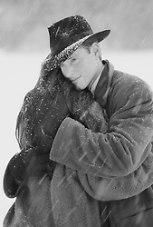 man and woman embracing during a snowstorm