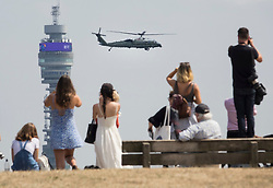 © Licensed to London News Pictures. 12/07/2018. London, UK. People watch from the top of Primrose Hill as President Trump comes into land on Marine One at the Regent's Park home of the US Ambassador at the start of his visit to the UK.  Photo credit: Peter Macdiarmid/LNP