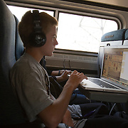 A young man travels by train with his Macbook Pro laptop computer and headphones.