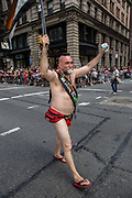 """New York, NY - 25 June 2017. New York City Heritage of Pride March filled Fifth Avenue for hours with groups from the LGBT community and it's supporters. A man dressed minimally, with a banner declaring him """"Mr. Stonewall Bear."""""""
