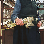 An elderly Romanian peasant holds a bunch of organically grown garlic, Botiza, Maramures, Romania. 90% of vegetable production is grown in small household plots and mainly used for self-consumption and for sale on local markets.