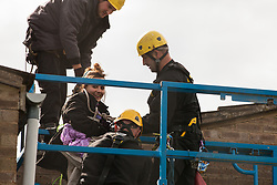Bailiffs use a cherry picker to evict a housing activist who had taken refuge on a roof on the Sweets Way housing estate on 23rd September 2015 in London, United Kingdom. A group of housing activists calling for better social housing provision in London had occupied some of the properties on the 142-home estate in Whetstone, in some cases refurbishing properties intentionally destroyed by the legal owners following eviction of the original residents, in order to try to prevent the eviction of the last resident on the estate and the planned demolition and redevelopment of the entire estate by Barnet Council and Annington Property Ltd.