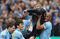 Football - 2013 / 2014 Premier League - Manchester City vs. West Ham United<br /> Manuel Pellegrini Manager of Manchester City is carried by Vincent Kompany and team mates as they celebrate winning the Barclays Premier League at the Etihad Stadium, Manchester